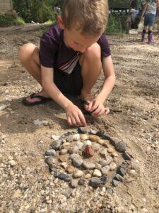 boy making rock mandala