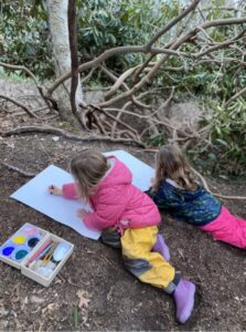 artists in the forest children painting in nature